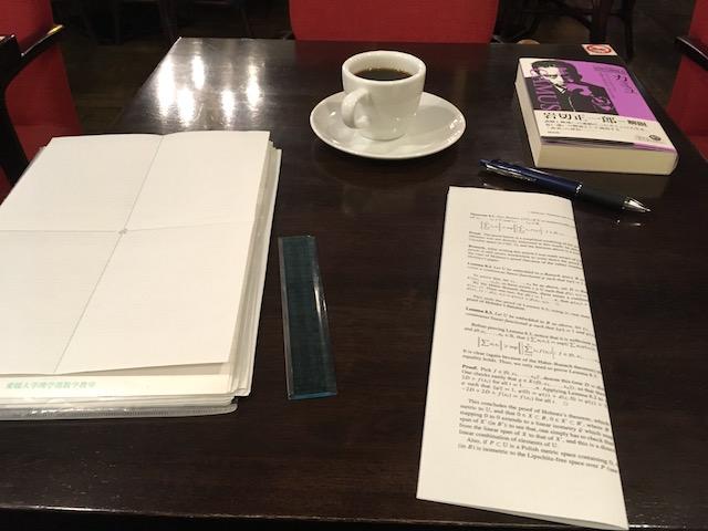 カフェのテーブル・コーヒーカップ・本・ペン・コピー用紙の裏紙・アクリル製の定規